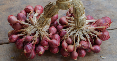 red onions: bunch of small red onions,Thai onions on wooden floor