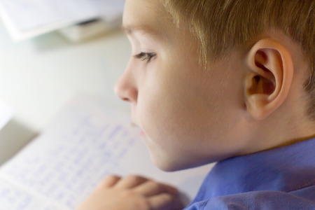 Close-up of boy hand with pencil writing english words by hand on traditional white notepad paper. Boy writes a letter to a friend