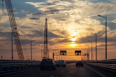 Riding a car over a bridge at sunset. Seagulls sit on lighting poles