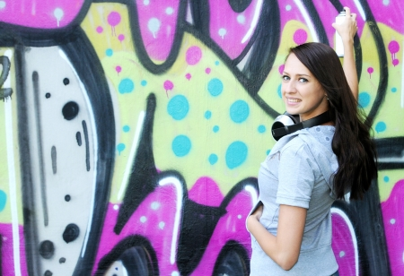 Young and beautiful girl posing against wall with graffiti photo
