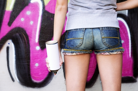 writers: Girl holding spray against graffiti wall Stock Photo