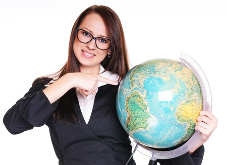 Pretty young teacher with globe over white background photo