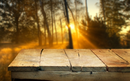 Empty wooden table and defocused autumn dawn in background  Great for product display montages