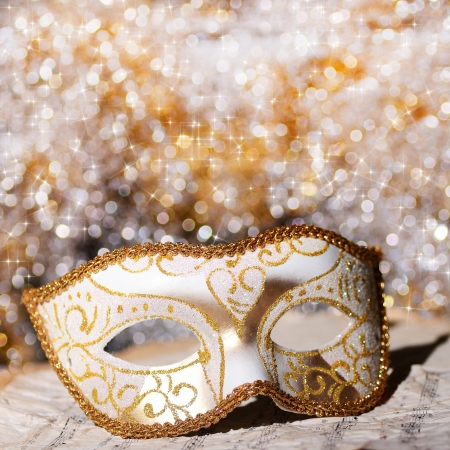 masquerade masks: Carnival mask on old paper with tunes and bokeh circles on background Stock Photo