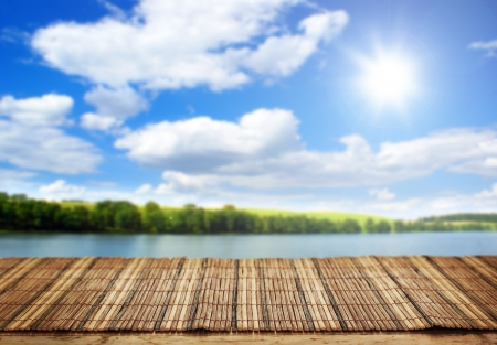 finite: Empty bamboo table and summer lakel in background  Stock Photo