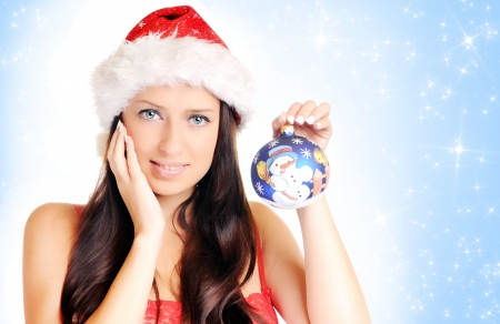 Beautiful girl in christmas hat over blue background with stars