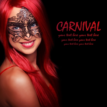 Beautiful red haired woman in carnival mask over black background photo