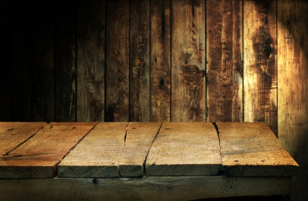 Empty wooden table and dark brown plank wall in background photo