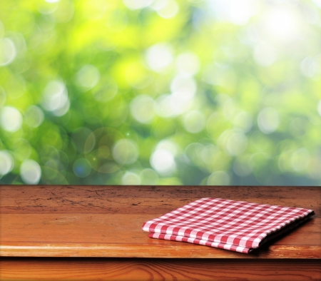 Empty wooden table and green spring background photo