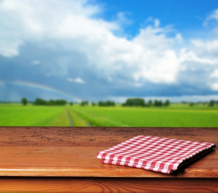 Empty wooden table and beautiful summer landscape in background. Great for product display montages photo