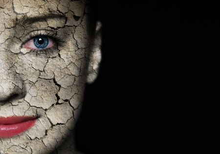crackle: Woman face covered with cracked earth texture - symbol of nature disaster or skin care Stock Photo