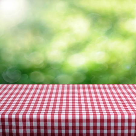 picnic cloth: Empty table and defocused foliage green background. Great for product display montages. Stock Photo