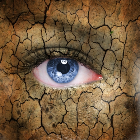 Cracked earth pattern on human face with blue eye. photo