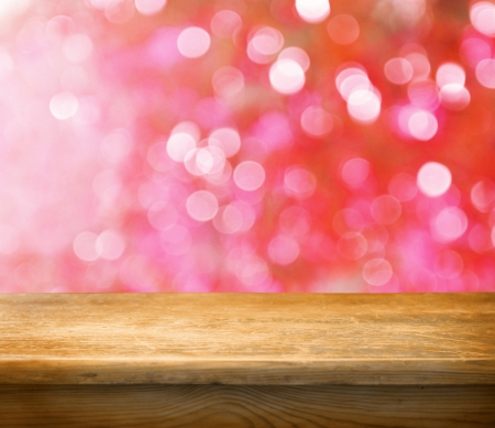 seasonal light display: Empty wooden deck table with red bokeh background. Ready for product display montage.