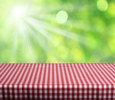 Empty table with red gingham tablecloth over green bokeh background. Great for product display montages
