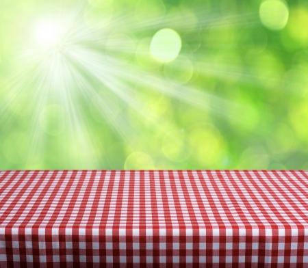 Leere Tabelle mit rot karierten Tischdecke über grüne Bokeh Hintergrund. Ideal für Produkt-Display Montagen Standard-Bild