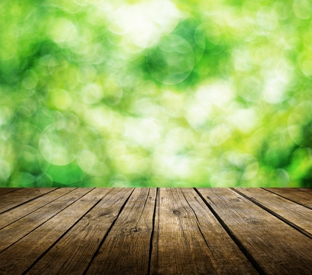 Wooden deck table over beautiful green background