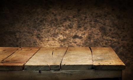 Leere hölzerne Deck Tisch mit braunen Wand im Hintergrund. Bereit für die Warenpräsentation montage. Standard-Bild