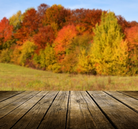 Empty wooden deck table with autumn background. Ready for product display montage. photo
