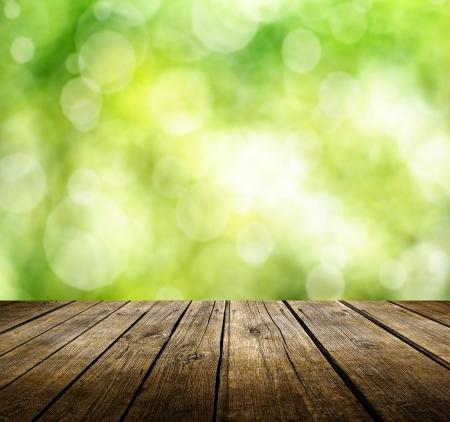 Leere hölzerne Deck Tisch mit grünen Hintergrund Frühjahr. Bereit für die Warenpräsentation montage. Standard-Bild