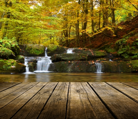 Empty wooden deck table with autumn waterfall background. Ready for product display montage.