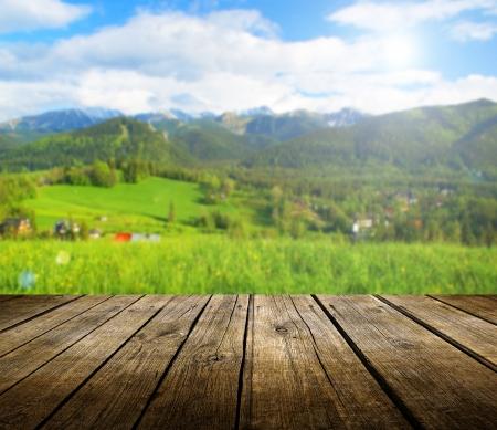 Leere hölzerne Deck Tisch mit Sommer Hintergrund. Bereit für die Warenpräsentation montage. Standard-Bild