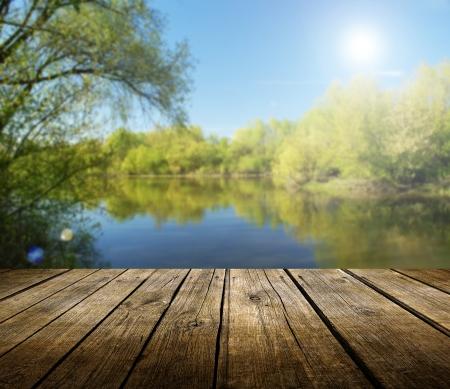 경치: 배경 봄 호수와 빈 나무 갑판 테이블. 제품 디스플레이 몽타주에 대 한 준비.