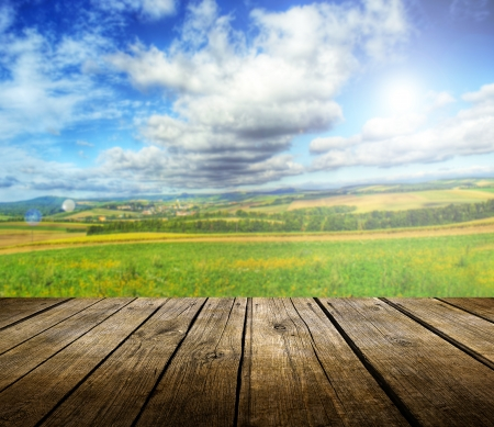 Empty wooden deck table with summer landscape in background. Ready for product display montage.  Standard-Bild