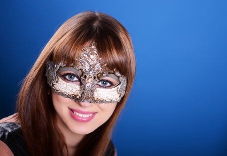 Beautiful caucasian brunette in carnival mask over blue background photo