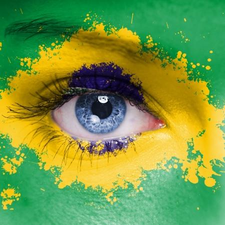 女性の顔に描かれたブラジルの国旗