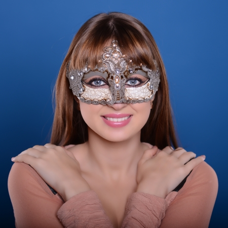 Beautiful caucasian brunette in carnival mask over blue  photo