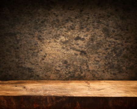 Empty wooden table and dark brown wall in background Standard-Bild
