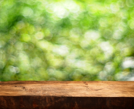 Empty wooden table and green summer background