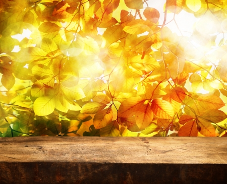 Leere Holztisch und schönen Herbst Blätter im Hintergrund