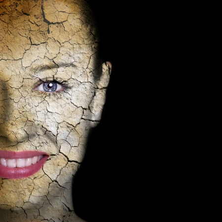 human skin texture: Woman face covered with cracked earth texture- symbol of dry skin