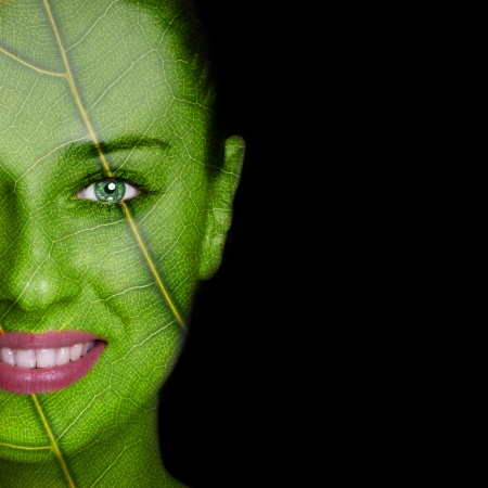 Nature concept - woman face covered with leaf texture photo