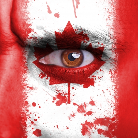 Canada flag painted on angry man face photo