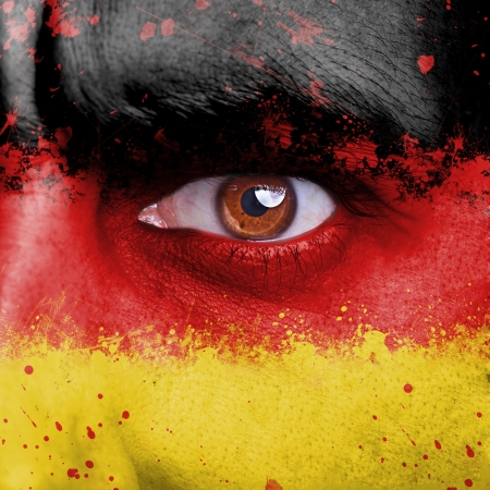 Germany flag painted on angry man face photo