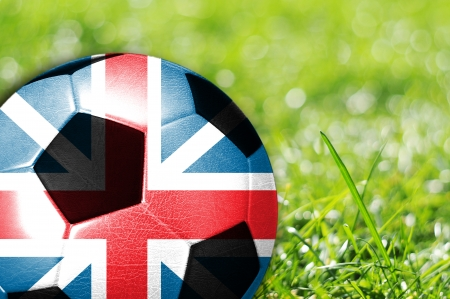 Soccer ball on grass with flag of England painted on it photo