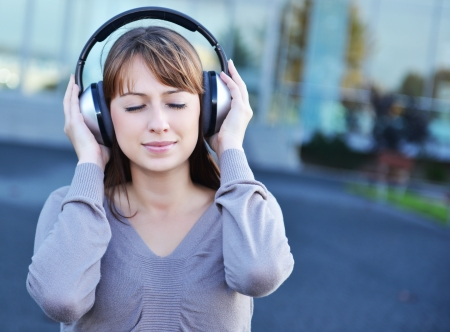 Beautiful girl in headphones over urban background photo