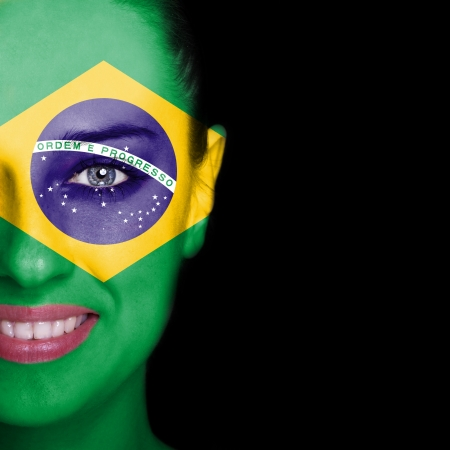 Brazil flag painted on smiling woman face photo