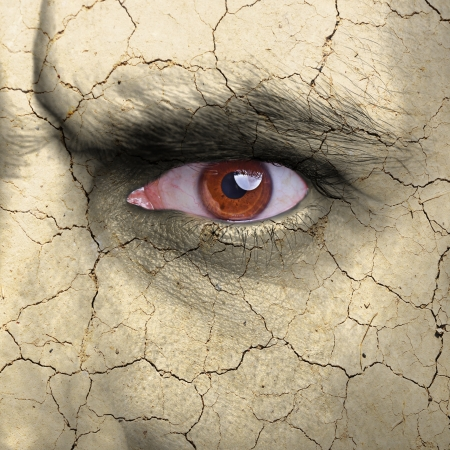 Beauty concept - face covered with cracked surface - symbol of dry skin photo