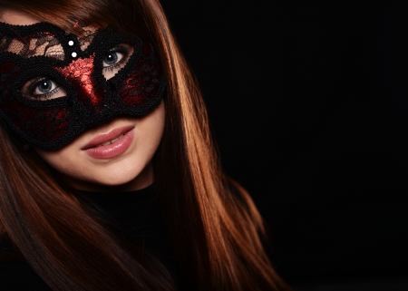 mysterious woman: Beautiful caucasian brunette in red carnival mask over black background Stock Photo