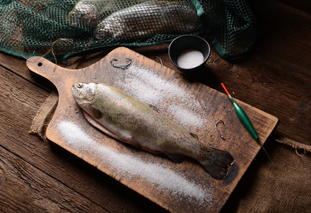 fish husbandry: Fresh trouts on wooden background Stock Photo