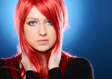 light complexion: Beautiful red haired woman posing over blue background Stock Photo