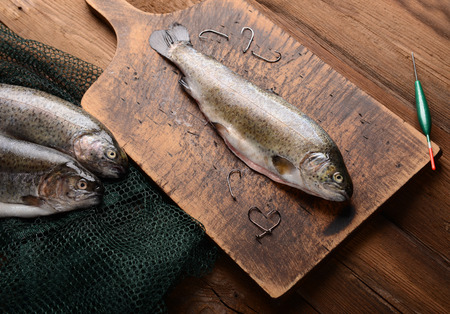 rearing of fish: Fresh trouts on wooden background Stock Photo