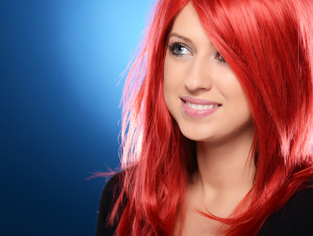 Beautiful red haired woman posing over blue background photo