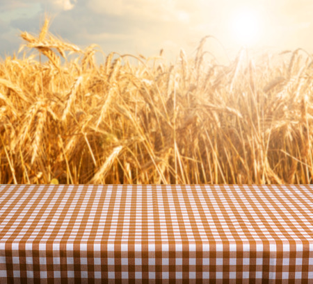 photomontage: Empty table and defocused wheat field inbackground Stock Photo