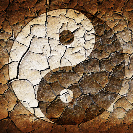 The Ying Yang sign painted on cracked earth  photo