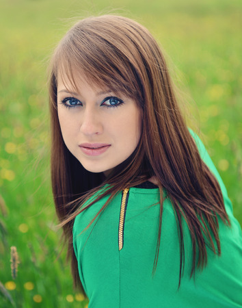 vouge: beautiful brunette posing against fresh green background